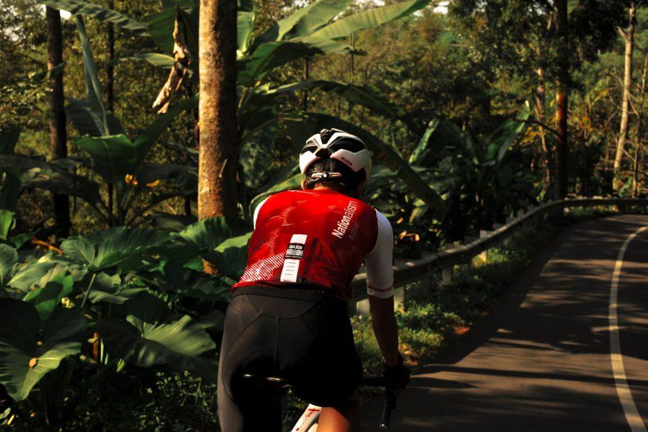 Mann auf Rad mit geolsterter Radhose im roten Trikot.